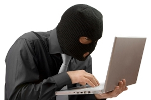 Masked burglar in front of a laptop