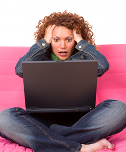 Woman sitting in front of laptop, looking stressed and overwhelmed