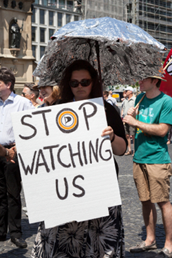 woman-holding-stop-watching-us-sign